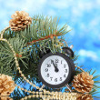 Green Christmas tree and clock on blue - Stockfoto