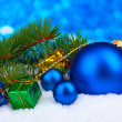 Christmas ball and toy with green tree in the snow on blue — Stock Photo #8121125
