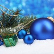 Christmas ball and toy with green tree in the snow on blue — Stock Photo