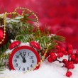Green Christmas tree with toy and clock in the snow on red — Stock Photo #8121158