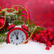 Green Christmas tree with toy and clock in the snow on red — Stock Photo #8121161
