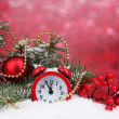 Green Christmas tree with toy and clock in the snow on red — Stock Photo #8121201