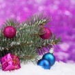 Christmas ball and toy with green tree in the snow on purple — Stock Photo