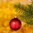 Christmas ball on the tree on yellow - Stok fotoğraf