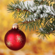 Christmas ball on the tree on yellow - Stock Photo