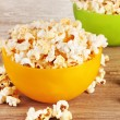 Popcorn in bright plastic bowls on wooden table — Stock Photo #8121895