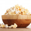 Popcorn in wooden bowl on wooden table on white background — Stock Photo