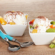 Delicious vanilla ice cream with chocolate and fruits in bowls and spoons o — Stock Photo
