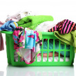 Clothes in green plastic basket isolated on white - Stock Photo