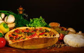 Delicious pizza dough, spices and vegetables on wooden table on brown backg — Stock Photo