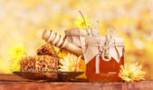 Two jars of honey,honeycombs and wooden drizzler on table on yellow backgro — Stock Photo