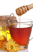 Honey and cup of tea isolated on white — Stock Photo