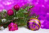 Palla di Natale e giocattolo con albero verde in mezzo alla neve su viola — Foto Stock
