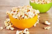 Popcorn in bright plastic bowls on wooden table — Stock Photo