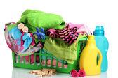 Roupas com detergente e na cesta de plástico verde, isolado no branco — Foto Stock