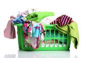 Clothes in green plastic basket isolated on white — Stock Photo