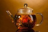 Bule de vidro com o exótico chá verde na mesa de madeira no fundo marrom — Foto Stock
