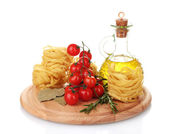 Noodles, jar of oil, spices and vegetables on wooden board isolated on whit — Stock Photo
