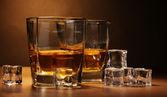 Iki bardak scotch viski ve buz üzerinde kahverengi zemin ahşap tablo — Stok fotoğraf