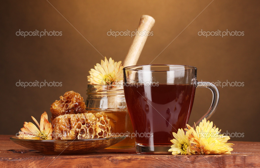 Honey, lemon, honeycomb and a cup of tea on wooden table on brown background  Stock Photo #8120393