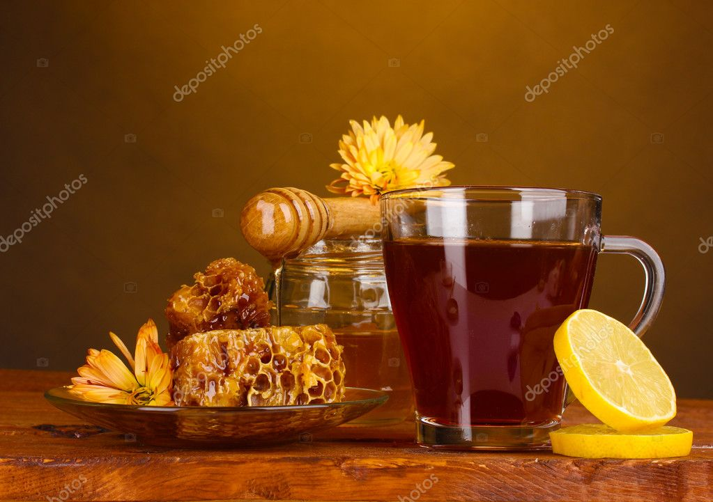 Honey, lemon, honeycomb and a cup of tea on wooden table on brown background — Stock Photo #8120397