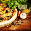 Delicious pizza, vegetables and spices on wooden table — Stock Photo #8144746