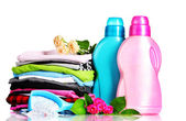 Detergent with washing powder and pile of colorful clothes isolated on whit — Stock Photo