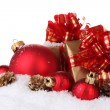 Beautiful red Christmas balls, gifts and cones on snow isolated on white - Stockfoto