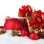 piękne czerwone bombki, prezenty i stożki na śniegu na białym tle — Zdjęcie stockowe