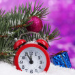 Royalty-Free Stock Photo: Green Christmas tree with toy and clock in the snow on purple