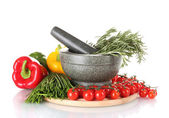 Rosemary in mortar, tomatoes cherry on wooden board, paprika and green onio — Stock Photo