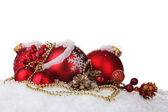 Piękne czerwone bombki i stożki na śniegu na białym tle — Zdjęcie stockowe
