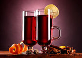 Mulled wine in the glasses, spice and lemon on purple background — Stock Photo
