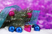 Green Christmas tree with toy and ribbon in the snow on purple — Stock Photo