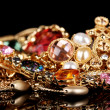 Various gold jewellery on black background — Foto Stock
