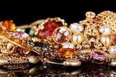 Verschillende gouden sieraden op zwarte achtergrond — Stockfoto