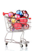 Beautiful bright Christmas balls in the cart isolated on white — Stock Photo