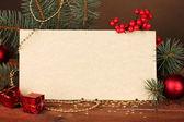 Leere postkarte, weihnachtskugel und tanne auf holztisch auf braun backg — Stockfoto