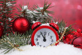 Green Christmas tree with toy and clock in the snow on red — Stock Photo
