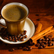 Golden cup with coffee, cinnamon and coffee beans on wooden table — Stok fotoğraf