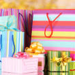 Bright gift bags and gifts on yellow background - Stockfoto