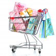 Shopping cart with bright gifts and paper bags isolated on white - Stock Photo