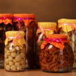 Delicious marinated mushrooms in the glass jars on wooden shelf - Photo