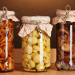 Delicious marinated mushrooms in the glass jars on wooden shelf - Foto de Stock