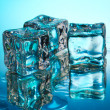 Melting ice cubes on blue background — ストック写真