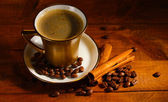 Golden cup with coffee, cinnamon and coffee beans on wooden table — Stock Photo