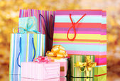 Bright gift bags and gifts on yellow background — Stock Photo