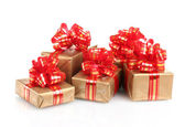 Beautiful golden gifts with red ribbon isolated on white — Stock Photo