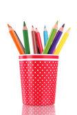 Renkli kalemler üzerinde beyaz izole kırmızı cam — Stok fotoğraf