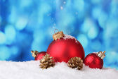 Beautiful blue Christmas balls and branch in snow on blue background — Stock Photo